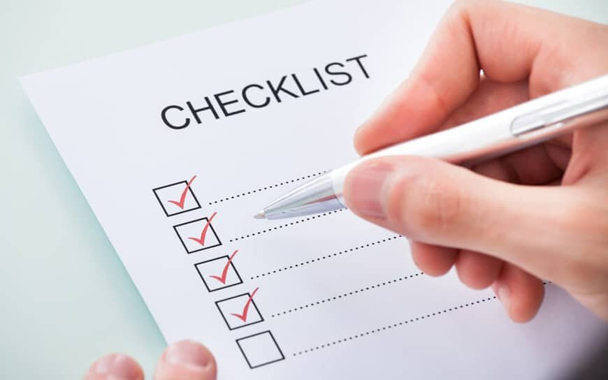 hand holding pen over paper with checklist