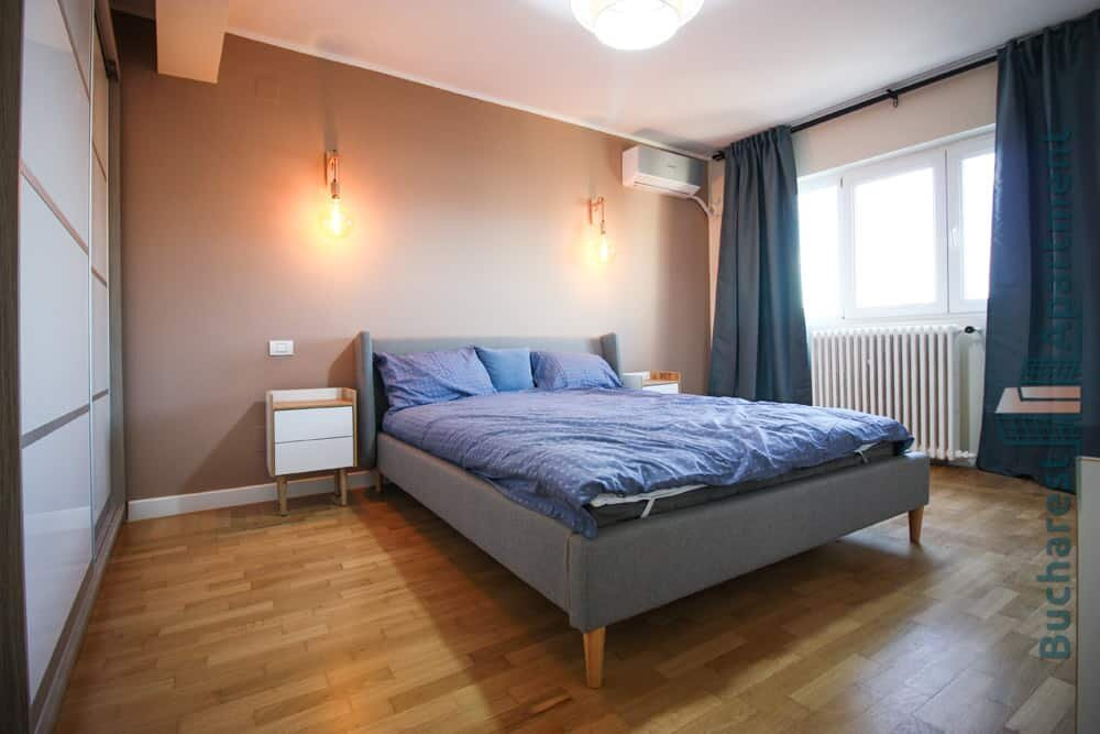 big bedroom with grey bad and blue curtains